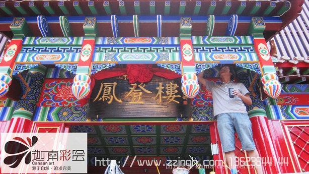 北京全聚德仿古建筑彩画艺术绘制现场案例,河南迦南艺术景观艺术工程,本案例以明清盛世典型旋子彩绘,等级次于和玺彩画。画面用简化形式的涡卷瓣旋花,有时也可画龙凤,两边用《》框起,可以贴金粉,也可以不贴金粉。一般用次要宫殿或寺庙中。旋子彩画俗称学子、蜈蚣圈,等级仅次于和玺彩画,其最大的特点是在藻头内使用了带卷涡纹的花瓣,即所谓旋子。旋子彩画最早出现于元代,明初即基本定型,清代进一步程式化,是明清官式建筑中运用最为广泛的彩画类型。旋子彩画在每个构件上的画面均划分为枋心、藻头和箍头三段。这种构图方式早在五代时
